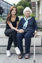 Portrait of smiling woman sitting with granddaughter on bench outdoors - MASF04656
