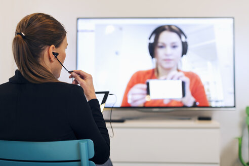 Rear view of businesswoman using in-ear headphones during conference call in creative office - MASF04659