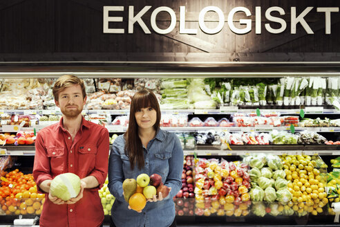 Portrait of young couple holding fresh vegetables in supermarket - MASF04662