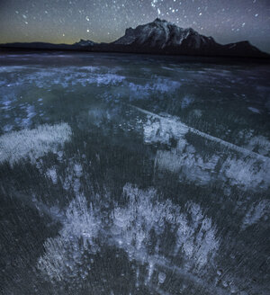 High angle view of methane bubbles in Abraham Lake by mountains during night - CAVF38627