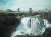 Majestic view of waterfall at White River Falls State Park against sky - CAVF38651