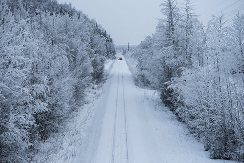 Distant view of vehicle on snow covered road by trees - CAVF38684