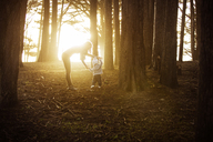 Mother assisting baby boy in walking at forest - CAVF38792