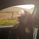 Carefree woman enjoying road trip in car at countryside - CAVF38849