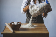 Midsection of woman removing flour from packet on table against wall - CAVF38957