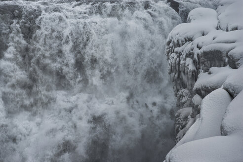 Scenic view of waterfall by snow covered cliff - CAVF38984