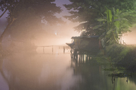 Stilt house on lake in forest during foggy weather - CAVF39032