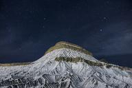 Scenic view of snowcapped mountain against starry sky at night - CAVF39035