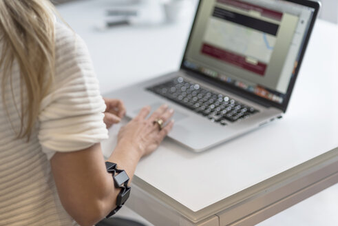 Woman with wearable at her arm using laptop at desk - PAF01816