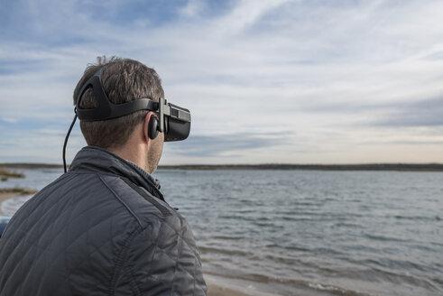 Man wearing VR glasses at lakeshore - PAF01825