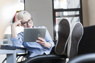 Smiling woman using tablet in office - UUF13355