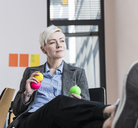 Businesswoman holding juggling balls in office - UUF13361