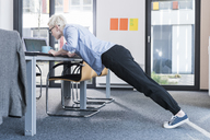 Businesswoman in office doing push ups on desk - UUF13364