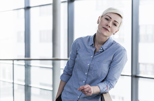 Portrait of woman in office building leaning on railing - UUF13367