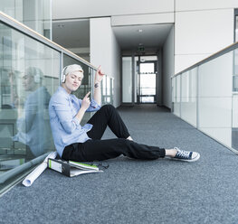 Woman sitting on office floor enjoying listening to music with headphones - UUF13370