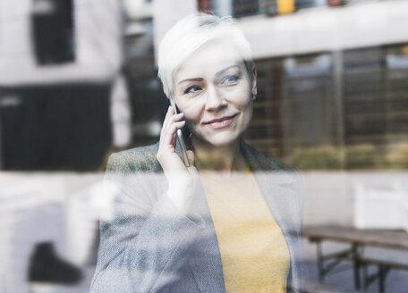 Portrait of confident businesswoman on cell phone behind windowpane - UUF13382