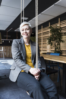 Portrait of smiling casual businesswoman sitting on swing in lounge - UUF13388