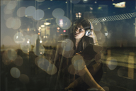 Young woman with tablet and headphones sitting outdoors at night - UUF13397
