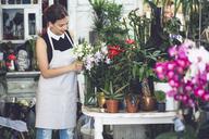 Female florist arranging flowers in shop - CAVF39145