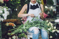 Midsection of florist cutting stems of roses at shop - CAVF39169