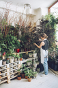 Rear view of florist examining potted plants at flower shop - CAVF39175