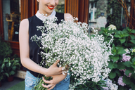 Midsection of florist holding white flowers at shop - CAVF39178