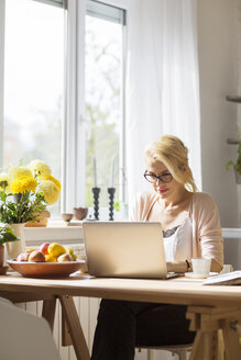 Woman using laptop computer while sitting at table by window - CAVF39184