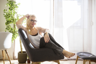 Thoughtful woman looking away while relaxing on arm chair - CAVF39208