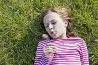 High angle view of cute girl blowing dandelion while lying on grassy field in park - CAVF39328