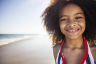 Close-up portrait of girl standing at beach against sky - CAVF39346