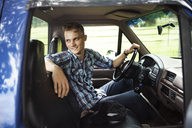 Happy man looking away while sitting in pick-up truck - CAVF39391