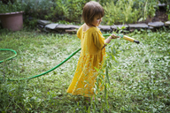 Girl watering plants with hose in backyard - CAVF39403