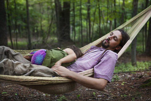 Father and daughter sleeping on hammock in forest - CAVF39418