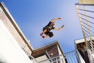 Low angle view of man jumping on buildings against clear blue sky - CAVF39430