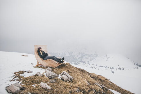 Austria, Kitzbuehel, Kitzbuehel Horn, young woman relaxing on deckchair in winter looking at view - GUSF00628