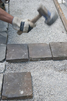 Man paving a way, cobblestones, hammering - CRF02784