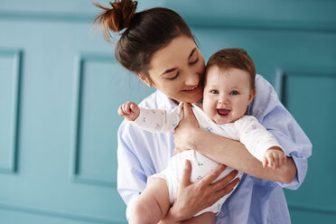 Happy mother carrying her baby at home - ABIF00305