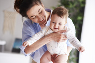 Happy mother carrying her baby at home - ABIF00311