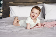Happy baby lying on bed at home - ABIF00317
