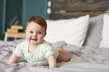 Portrait of happy baby lying on bed at home - ABIF00320