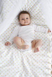 Portrait of content baby lying in crib - ABIF00323
