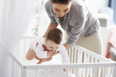 Mother laying her baby into crib at home - ABIF00326