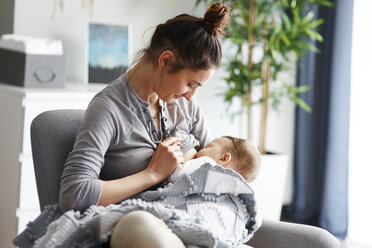 Mother breastfeeding her baby at home - ABIF00329