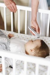 Mother with digital thermometer checking temperature of baby in crib - ABIF00332