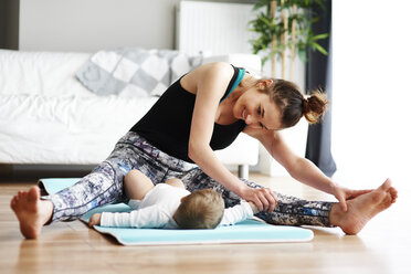 Mother with baby exercising on yoga mat at home - ABIF00335