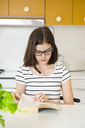 Girl reading a book in kitchen - LVF06864