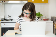 Girl using laptop and looking at a book in kitchen - LVF06867