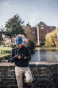 Senior man with cycling helmet using smartphone - GUSF00635