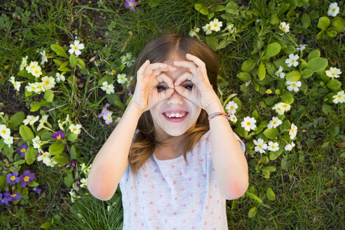 Girl looking through fingers, lying on flower meadow, top view - LVF06871