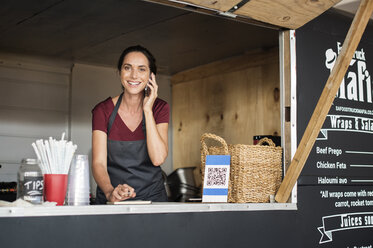 Portrait of smiling female vendor talking on smart phone while working in food truck - CAVF39485